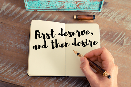 deserve: Retro effect and toned image of a woman hand writing on a notebook. Handwritten quote First deserve, and then desire as inspirational concept image