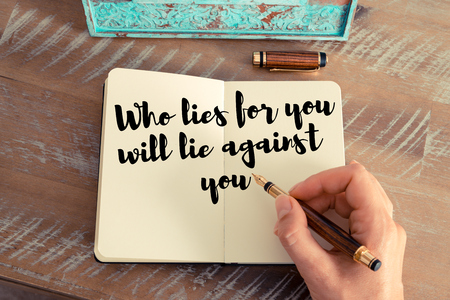 Retro effect and toned image of a woman hand writing on a notebook. Handwritten quote Who lies for you will lie against you as inspirational concept image