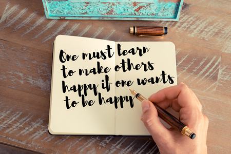 one person with others: Retro effect and toned image of a woman hand writing on a notebook. Handwritten quote One must learn to make others happy if one wants to be happy as inspirational concept image Stock Photo