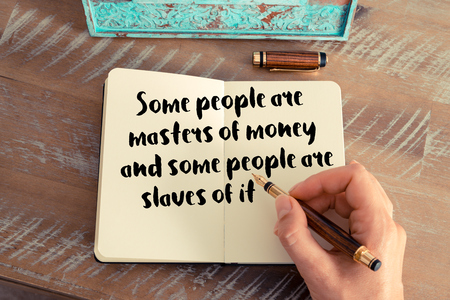 slaves: Retro effect and toned image of a woman hand writing on a notebook. Handwritten quote Some people are masters of money and some people are slaves of it as inspirational concept image