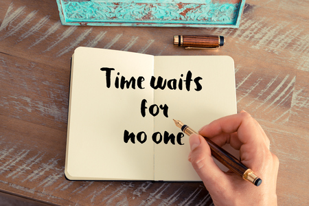 waits: Retro effect and toned image of a woman hand writing on a notebook. Handwritten quote Time waits for no one as inspirational concept image