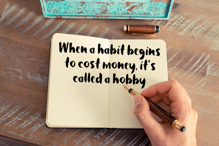 begins: Retro effect and toned image of a woman hand writing on a notebook. Handwritten quote When a habit begins to cost money, its called a hobby as inspirational concept image