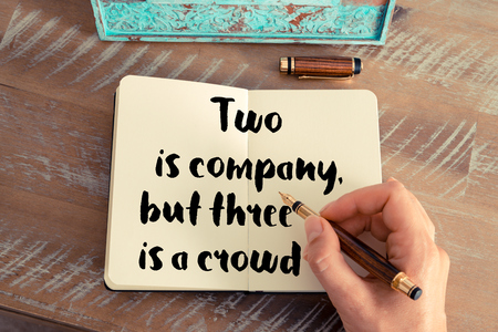 but think: Retro effect and toned image of a woman hand writing on a notebook. Handwritten quote Two is company, but three is a crowd as inspirational concept image