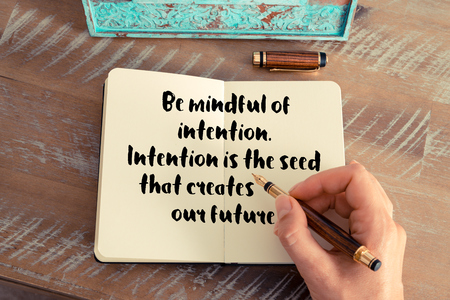 intention: Retro effect and toned image of a woman hand writing on a notebook. Handwritten quote Be mindful of intention. Intention is the seed that creates our future.  as inspirational concept image
