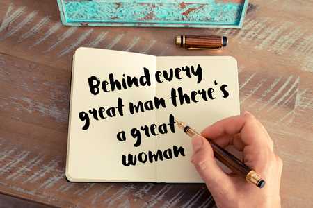 Retro effect and toned image of a woman hand writing on a notebook. Handwritten quote Behind every great man there's a great woman as inspirational concept image