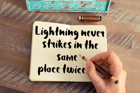 twice: Retro effect and toned image of a woman hand writing on a notebook. Handwritten quote Lightning never strikes in the same place twice as inspirational concept image