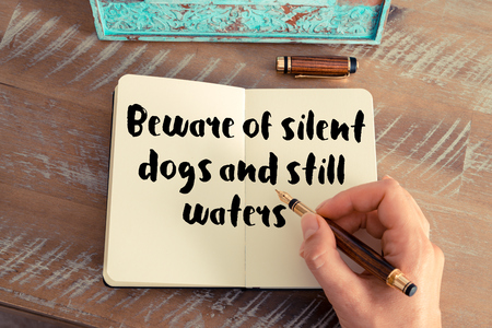 waters: Handwritten quote Beware of silent dogs and still waters as inspirational concept image Stock Photo