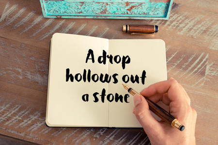 hollows: Handwritten quote A drop hollows out a stone as inspirational concept image