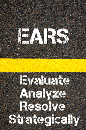 strategically: Concept image of Business Acronym EARS Evaluate Analyze Resolve Strategically written over road marking yellow paint line
