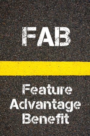 road marking: Concept image of Business Acronym FAB Feature Advantage Benefit written over road marking yellow paint line Stock Photo