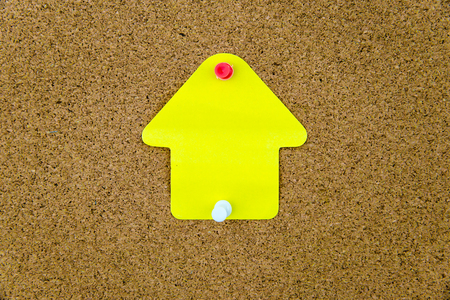 yellow thumbtacks: Blank yellow paper note in shape of house pinned on cork board with white and red thumbtacks, copy space available