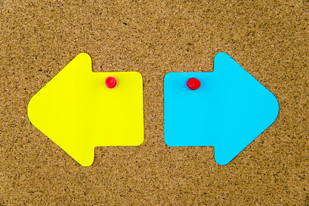 yellow thumbtacks: Blank yellow and blue paper notes in shape of opposite arrows pinned on cork board with thumbtacks, copy space available Stock Photo