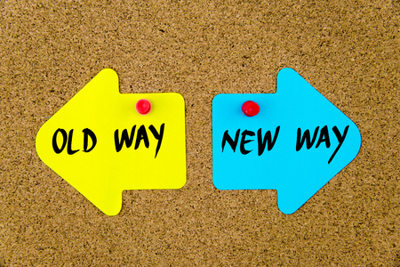 new way: Message OLD WAY versus NEW WAY on yellow and blue paper notes as opposite arrows pinned on cork board with thumbtacks. Choice conceptual image Stock Photo