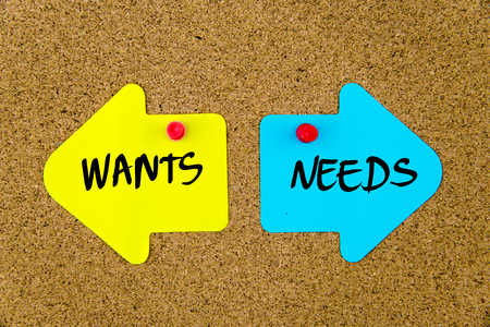 wants: Message WANTS versus NEEDS on yellow and blue paper notes as opposite arrows pinned on cork board with thumbtacks. Choice conceptual image
