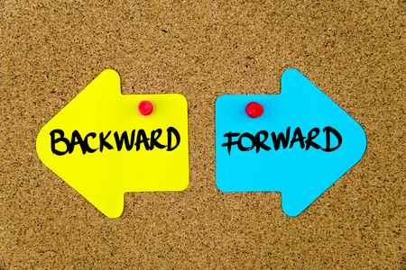 yellow thumbtacks: Message BACKWARD versus FORWARD on yellow and blue paper notes as opposite arrows pinned on cork board with thumbtacks. Choice conceptual image