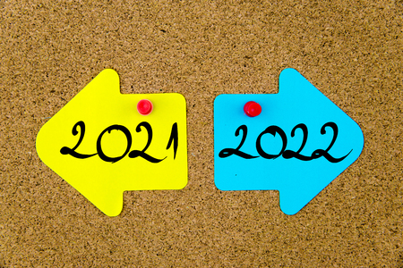 yellow thumbtacks: Message 2021 versus 2022 on yellow and blue paper notes as opposite arrows pinned on cork board with thumbtacks. Choice conceptual image Stock Photo