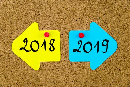 메시지 2018 대 2019는 노란색과 파란색 종이 노트에 반대 화살표가 압정으로 코르크 보드에 고정되어 있습니다. 선택 개념적 이미지 스톡 콘텐츠