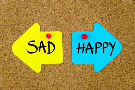 yellow thumbtacks: Message SAD versus HAPPY on yellow and blue paper notes as opposite arrows pinned on cork board with thumbtacks. Choice conceptual image