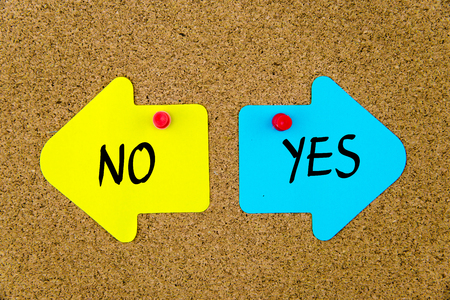 yellow thumbtacks: Message NO versus YES on yellow and blue paper notes as opposite arrows pinned on cork board with thumbtacks. Choice conceptual image Stock Photo