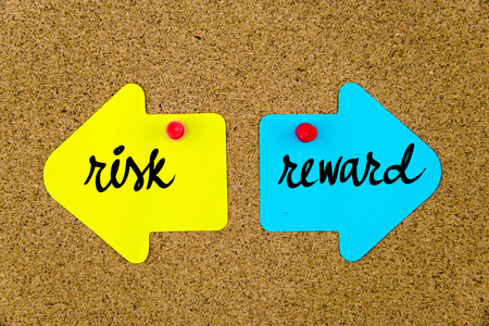 yellow thumbtacks: Message RISK versus REWARD on yellow and blue paper notes as opposite arrows pinned on cork board with thumbtacks. Choice conceptual image