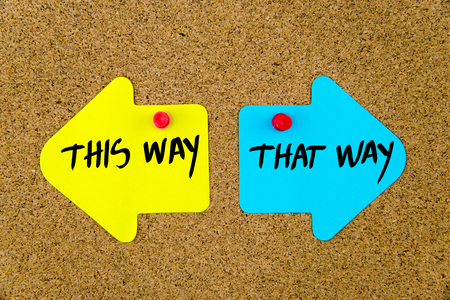 yellow thumbtacks: Message THIS WAY versus THAT WAY on yellow and blue paper notes as opposite arrows pinned on cork board with thumbtacks. Choice conceptual image Stock Photo