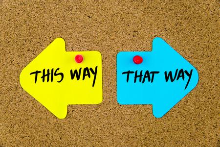 Wiadomość TEN SPOSÓB w porównaniu z TĄ DROGĄ na żółtych i niebieskich kartkach papieru jako przeciwnych strzałach przypiętych na tablicy korkowej z pinezkami. Wybór koncepcyjnego obrazu