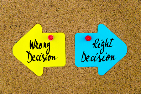 yellow thumbtacks: Message WRONG DECISION versus RIGHT DECISION on yellow and blue paper notes as opposite arrows pinned on cork board with thumbtacks. Choice conceptual image Stock Photo