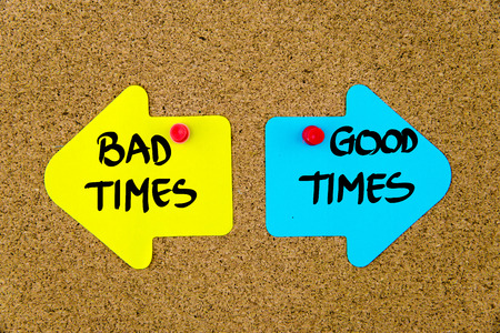 bad times: Message BAD TIMES versus GOOD TIMES on yellow and blue paper notes as opposite arrows pinned on cork board with thumbtacks. Choice conceptual image Stock Photo