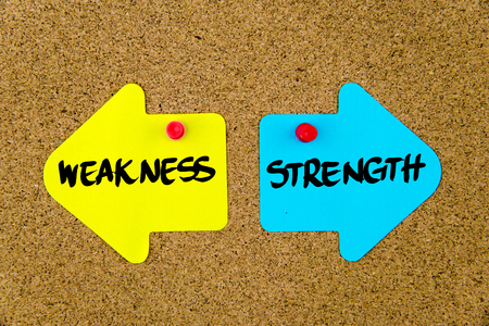 yellow thumbtacks: Message WEAKNESS versus STRENGTH  on yellow and blue paper notes as opposite arrows pinned on cork board with thumbtacks. Choice conceptual image
