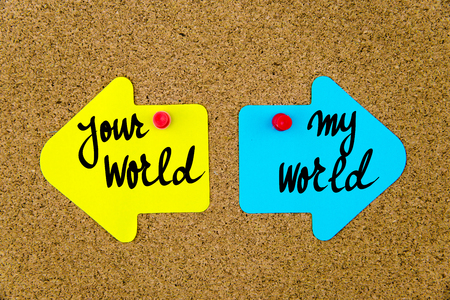 yellow thumbtacks: Message YOUR WORLD versus MY WORLD on yellow and blue paper notes as opposite arrows pinned on cork board with thumbtacks. Choice conceptual image
