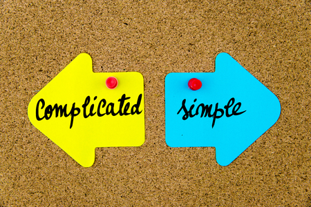 yellow thumbtacks: Message COMPLICATED versus SIMPLE  on yellow and blue paper notes as opposite arrows pinned on cork board with thumbtacks. Choice conceptual image