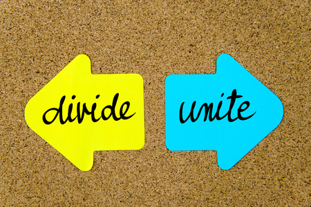 unite: Message Divide versus Unite on yellow and blue paper notes as opposite arrows pinned on cork board with thumbtacks. Choice conceptual image Stock Photo