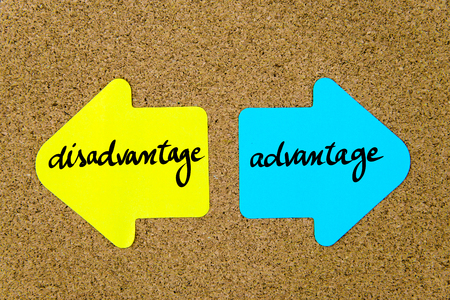 Message Disadvantage versus Advantage on yellow and blue paper notes as opposite arrows pinned on cork board with thumbtacks. Choice conceptual image Stock Photo