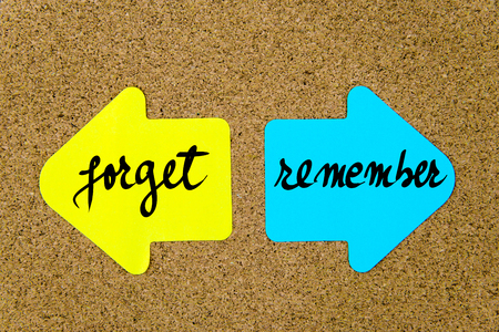 yellow thumbtacks: Message Forget versus Remember on yellow and blue paper notes as opposite arrows pinned on cork board with thumbtacks. Choice conceptual image