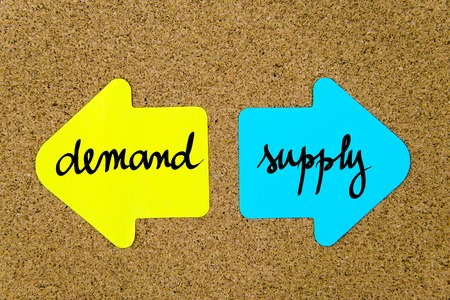 yellow thumbtacks: Message Demand versus Supply on yellow and blue paper notes as opposite arrows pinned on cork board with thumbtacks. Choice conceptual image Stock Photo