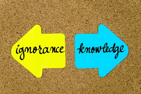 Message Ignorance versus Knowledge on yellow and blue paper notes as opposite arrows pinned on cork board with thumbtacks. Choice conceptual image