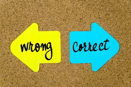 yellow thumbtacks: Message Correct versus Wrong on yellow and blue paper notes as opposite arrows pinned on cork board with thumbtacks. Choice conceptual image