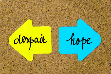 yellow thumbtacks: Message Despair versus Hope on yellow and blue paper notes as opposite arrows pinned on cork board with thumbtacks. Choice conceptual image