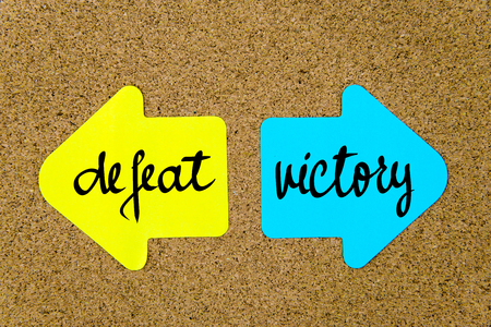 yellow thumbtacks: Message Defeat versus Victory on yellow and blue paper notes as opposite arrows pinned on cork board with thumbtacks. Choice conceptual image