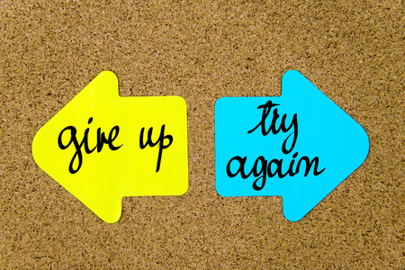 give up: Message Give Up versus Try Again on yellow and blue paper notes as opposite arrows pinned on cork board with thumbtacks. Choice conceptual image Stock Photo
