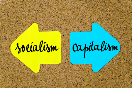 socialism: Message Socialism versus Capitalism on yellow and blue paper notes as opposite arrows pinned on cork board with thumbtacks. Choice conceptual image