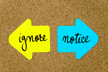 yellow thumbtacks: Message Ignore versus Notice on yellow and blue paper notes as opposite arrows pinned on cork board with thumbtacks. Choice conceptual image