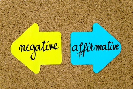 affirmative: Message Negative versus Affirmative on yellow and blue paper notes as opposite arrows pinned on cork board with thumbtacks. Choice conceptual image