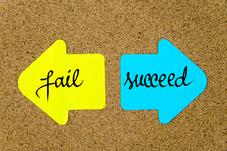 yellow thumbtacks: Message Fail versus Succeed on yellow and blue paper notes as opposite arrows pinned on cork board with thumbtacks. Choice conceptual image
