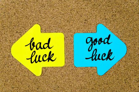 yellow thumbtacks: Message Bad Luck versus Good Luck on yellow and blue paper notes as opposite arrows pinned on cork board with thumbtacks. Choice conceptual image