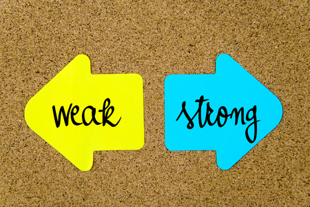 strong message: Message Weak versus Strong on yellow and blue paper notes as opposite arrows pinned on cork board with thumbtacks. Choice conceptual image