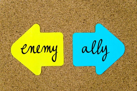 an ally: Message Enemy versus Ally on yellow and blue paper notes as opposite arrows pinned on cork board with thumbtacks. Choice conceptual image Stock Photo