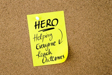 outcomes: Business Acronym HERO Helping Everyone Reach Outcomes written on  yellow paper note pinned on cork board with white thumbtack, copy space available Stock Photo