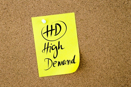 cork sheet: Business Acronym HD High Demand written on  yellow paper note pinned on cork board with white thumbtack, copy space available Stock Photo