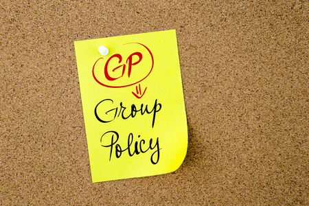 gp: Business Acronym GP Group Policy written on  yellow paper note pinned on cork board with white thumbtack, copy space available Stock Photo